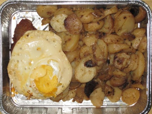 Hamburger Schnitzel unter einem Spiegelei, mit Bratkartoffeln
