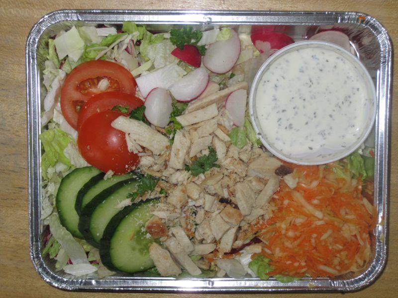 Salatplatte mit Gurke, Tomate, Radies, Putenstreifen und Dressing